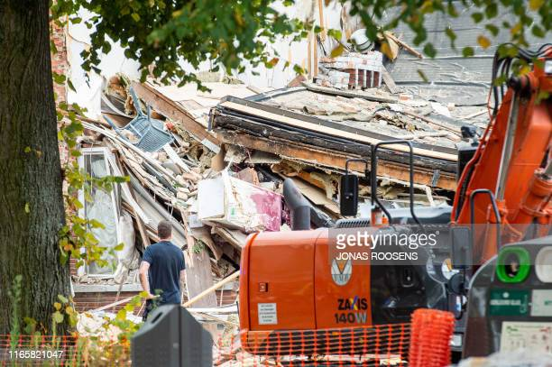 Man stands by the site of an explosion in the Antwerp district of Wilrijk, on September 3, 2019 after at least three houses were destroyed. - Police...