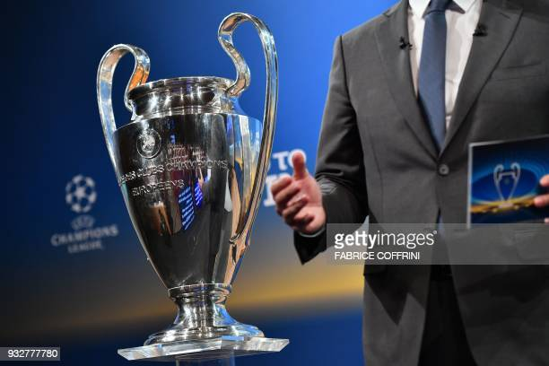 A man stands by the UEFA Champions League football cup during the draw for the quarter finals round of the UEFA Champions League football tournament...