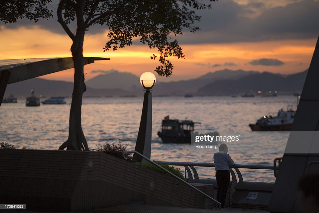 A man stands by the waterfront at sunset in Hong Kong, China, on Tuesday, June 18, 2013. A shortage of housing, low mortgage costs and a buying spree by mainland Chinese have led home prices to more than double since the beginning of 2009, shrugging off repeated attempts by the government to curb gains amid an outcry over affordability. Photographer: Jerome Favre/Bloomberg via Getty Images
