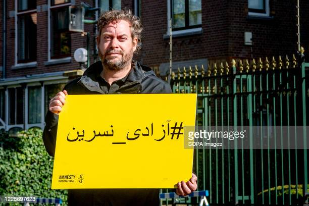A man stands displaying a placard with a message stating Free Nasrin Now in The Hague Amnesty International calls on the Iranian authorities at the...