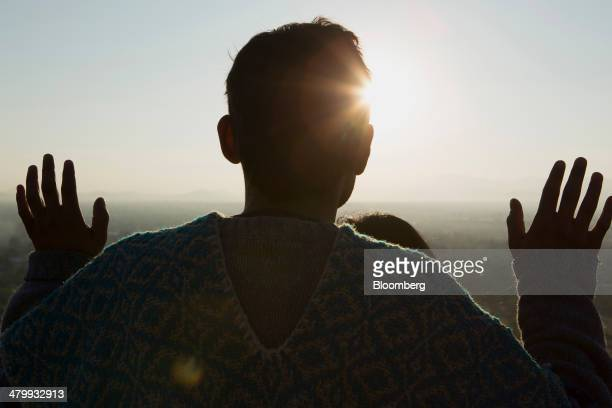 A man stands facing the sun at the top of the Pyramid of the Sun during celebrations for the Spring Equinox at the archaeological site of Teotihuacan...