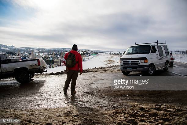 A man stands guard at the front gate as a line of cars enter the Oceti Sakowin Camp on the edge of the Standing Rock Sioux Reservation on December 3...