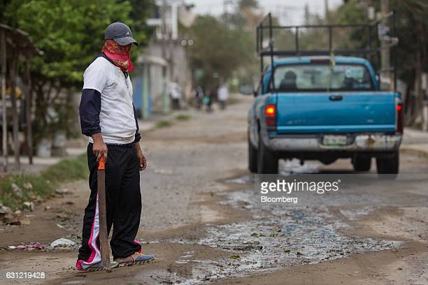 A man stands guard near his home after looting in Veracruz City Mexico on Saturday Jan 7 2017 Mexico's National Association Of Retail And Department...