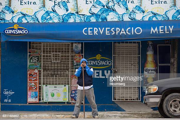 A man stands guard outside of a closed convenience store after looting in Veracruz City Mexico on Saturday Jan 7 2017 Mexico's National Association...