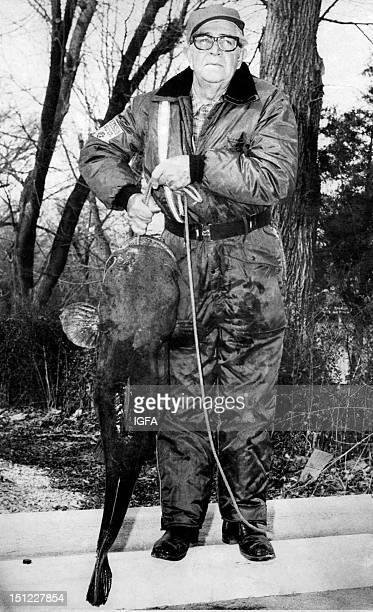 A man stands holding a 43 pound flathead catfish taken on 6 pound test line on March 6 1975 on Lake Norfork Arkansas