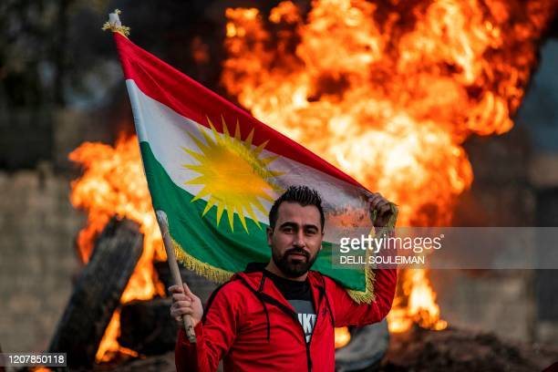 Man stands holding a Kurdish flag near a bonfire marking the Kurdish holiday of Noruz in Qamishli in Syria's northeastern Hasakah province on March...