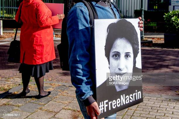 A man stands holding up a placard with a picture of Nasrin with a message below reading #FreeNasrin in The Hague Amnesty International calls on the...