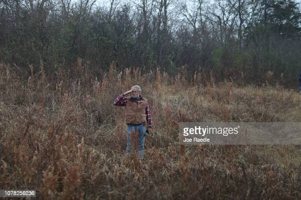 A man stands in a field and salutes as the train carrying former President George HW Bush to his final resting place passes by on December 6 2018 in...