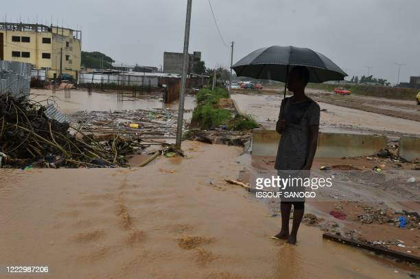 Man stands in a flooded street after heavy rains in Riviera Cocody, a residential district in Abidjan, on June 26, 2020.