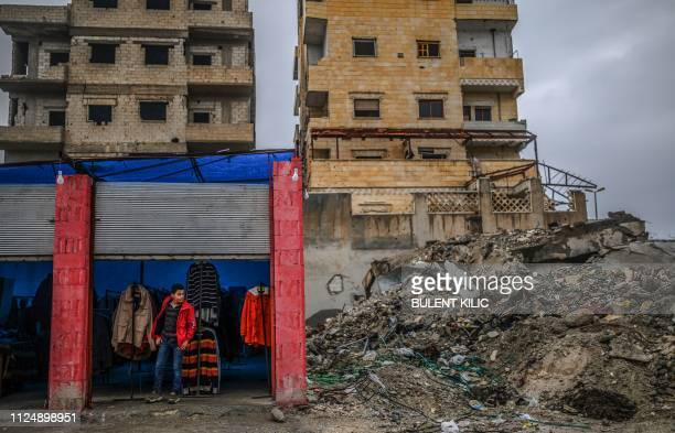 Man stands in a shop next to a building destroyed during battles in recent years in the northern Syrian city of Raqa, on February 14, 2019. - In...