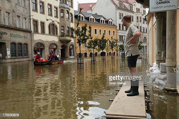 A man stands in a street flooded by the nearby Elbe river as rescue workers float by in a rubber boat in the historic city center on June 6 2013 in...