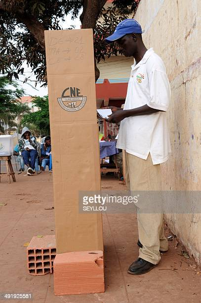 A man stands in a voting booth to vote in the second round of the presidential election on May 18 2014 in Bissau GuineaBissau voted for a new...