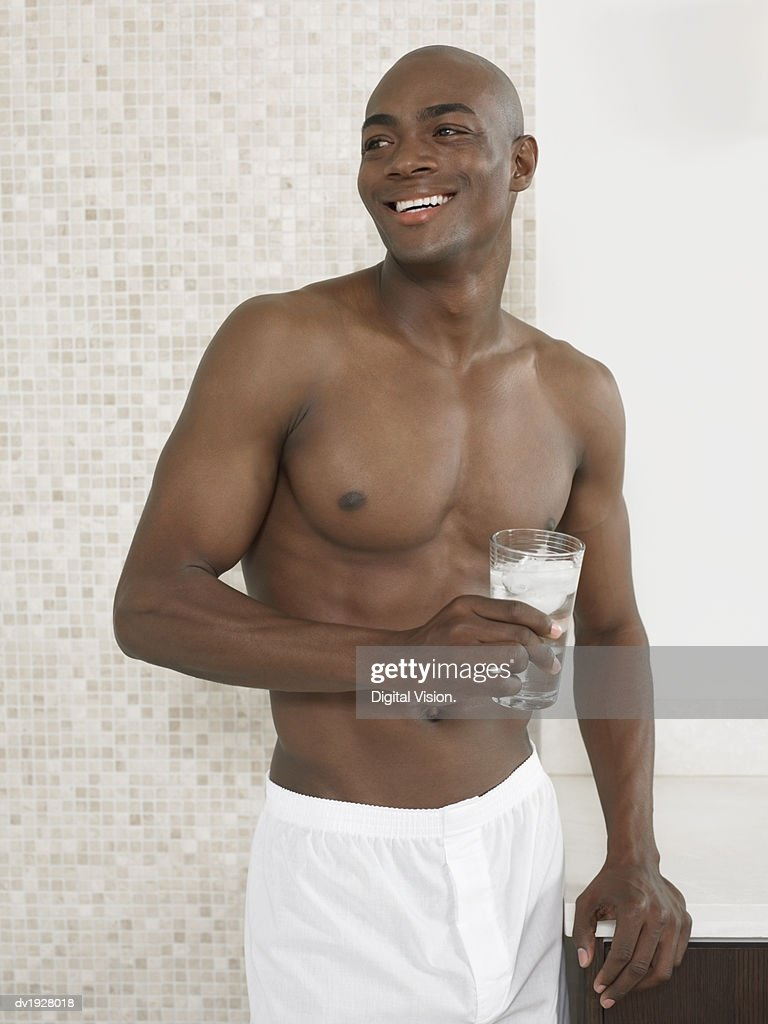 Man Stands in Bathroom in His Boxer Shorts Holding a Glass of Water : Stock Photo