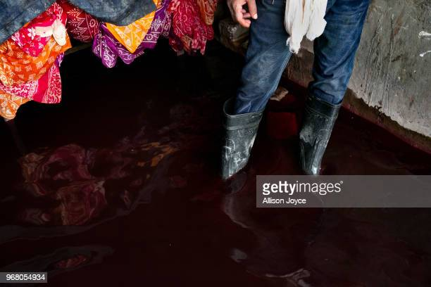 A man stands in dying color in a dying factory in Shyampur whose waste is dumped into the Buriganga river on June 4 2018 in Dhaka Bangladesh...