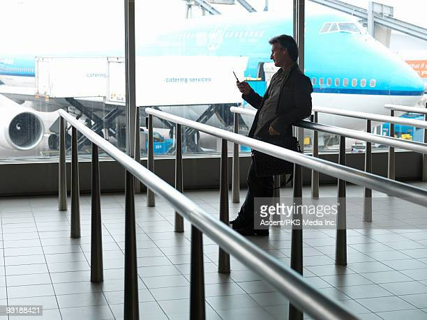 man stands in empty airport queue, text messaging - schiphol airport stock photos and pictures