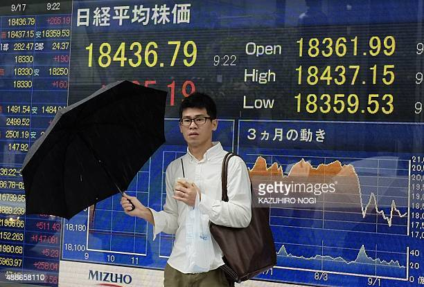 A man stands in front of a board showing the numbers on the Nikkei 225 index at the Tokyo Stock Exchange in Tokyo on September 17 2015 Tokyo shares...