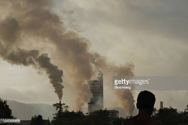 A man stands in front of a chemical factory as it discharges exhaust into the air of Mumbai India on Monday Sept 13 2010 China and India are the...