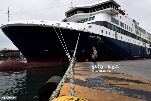 A man stands in front of a docked ferry at the port of Peiraeus during a 48hour strike by the sailor union on May 16 2017 Greek unions today kicked...