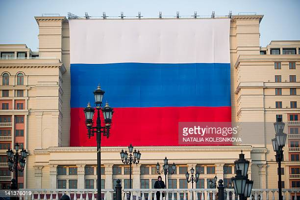 A man stands in front of a giant Russian national flag hanging on the Moskva Hotel's facade at the central Manezhnaya Square just outside the Kremlin...