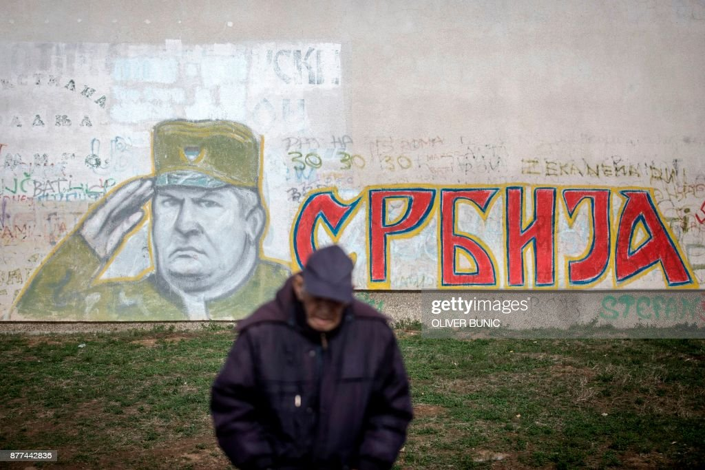 TOPSHOT - A man stands in front of a graffiti depicting former Bosnian Serb commander Ratko Mladic and reading 'Serbia' written in Cyrillic, painted on a wall in Belgrade on Nocember 22, 2017. Ratko Mladic, who was convicted of genocide on November 22, 2017, believed himself to be a crusading defender of the Serbs but was dubbed the 'Butcher of Bosnia' for mass slaughter at the hands of his forces. /