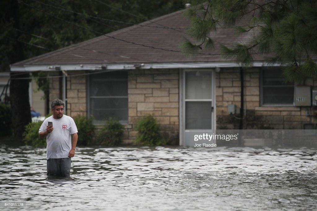 A man stands in front of a home surrounded by water after the flooding of Hurricane Harvey inundated the area on August 30, 2017 in Port Arthur, Texas. Harvey, which made landfall north of Corpus Christi late Friday evening, is expected to dump upwards to 40 inches of rain in Texas over the next couple of days.