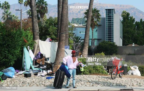 Man stands in front of a homeless encampment, with the Hollywood sign in the background, on September 23, 2019 in Los Angeles, California. A new plan...