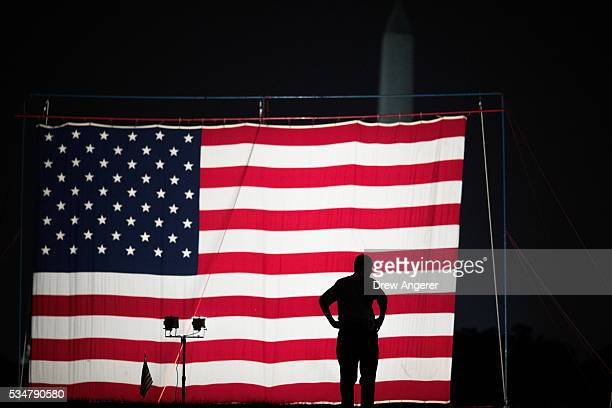 A man stands in front of a large American flag set up on the National Mall May 27 in Washington DC Rolling Thunder members and supporters will...