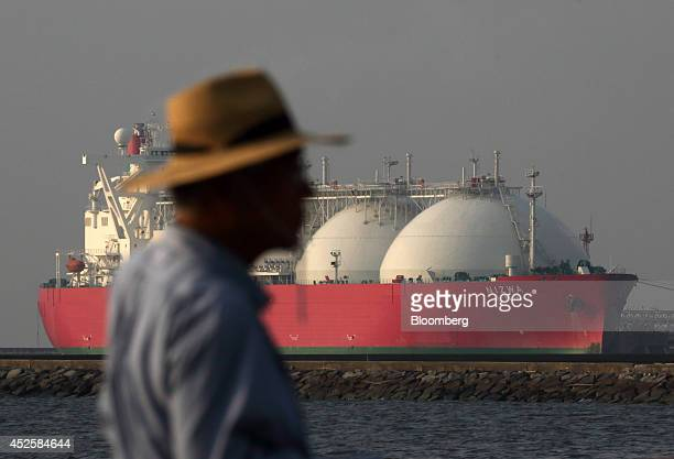 A man stands in front of a liquefied natural gas tanker berthed at Tokyo Electric Power Co's Futtsu gasfired thermal power plant in Futtsu Chiba...