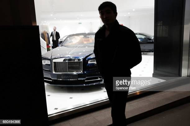 A man stands in front of a luxury car dealership on March 9 2017 in Moscow Russia Relations between the United States and Russia are at their lowest...