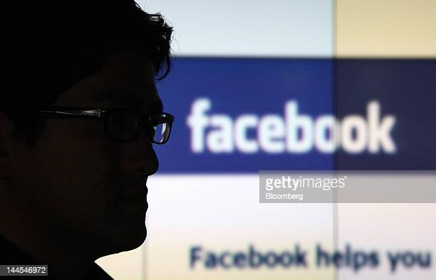A man stands in front of a monitor displaying the Facebook Inc website in this arranged photograph in Tokyo Japan on Wednesday May 16 2012 Facebook...
