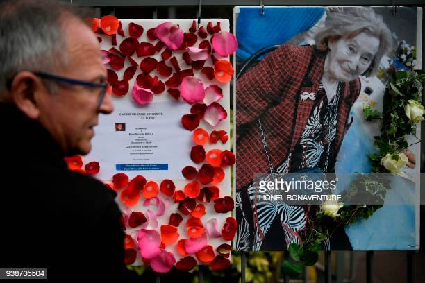 A man stands in front of a picture of Mireille Knoll and a message announcing a 'Marche Blanche' condemning the alleged antisemitic motive for of her...