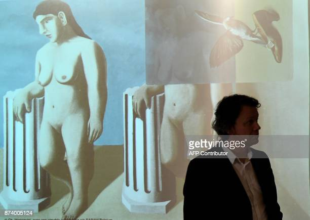 A man stands in front of a projection of the recomposed art work 'The Enchanted Pose' by Belgium artist Rene Magritte during a press conference...
