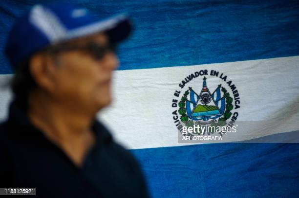 Man stands in front of a Salvadoran flag during a protest against the government of Nayib Bukele and demanding the resignation of all deputies at...