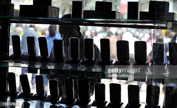 A man stands in front of a shop window displaying mobile phones on October 12012 in Nairobi as Kenya confirmed a switchoff of counterfeit mobiles...