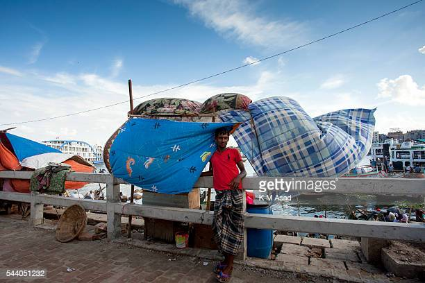 SADARGHAT DHAKA BANGLADESH A man stands in front of a temporary street shop at sadarghat launch terminal Bangladesh is one of the most densely...