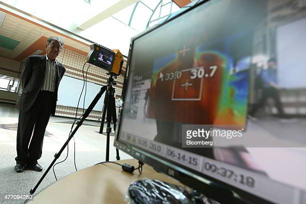 A man stands in front of a thermographic camera to have his temperature checked at a subway station in Bucheon South Korea on Sunday June 14 2015...