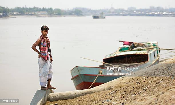 A man stands in front of a transport ship at the harbour of Khulna on April 11 2016 in Khulna Bangladesh