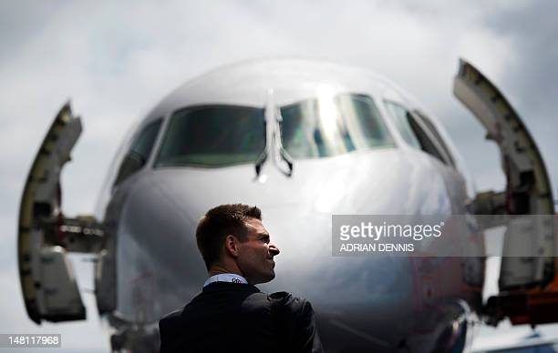 A man stands in front of Aeroflot jet during the second day at the Farnborough International Airshow in Hampshire southern England on July 10 2012 In...