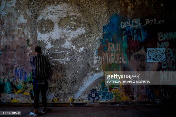 TOPSHOT A man stands in front of an artwork in memory of Brazilian activist Marielle Franco by Portuguese artist Vhils at the Monsanto panoramic...