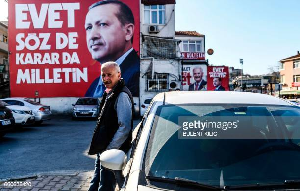 A man stands in front of an 'Event' campaign billboard bearing the portrait of Turkish President Recep Tayyip Erdogan on March 30 in Istanbul two...