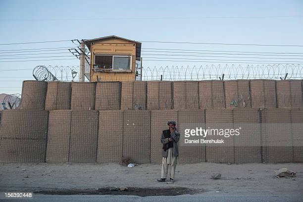 A man stands in front of blast walls as he waits for transport on November 14 2012 in Kabul Afghanistan