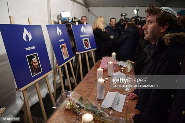 A man stands in front of candles and pictures of people killed in the deadly attack against the Hyper Cacher supermarket in 2015 during a ceremony...