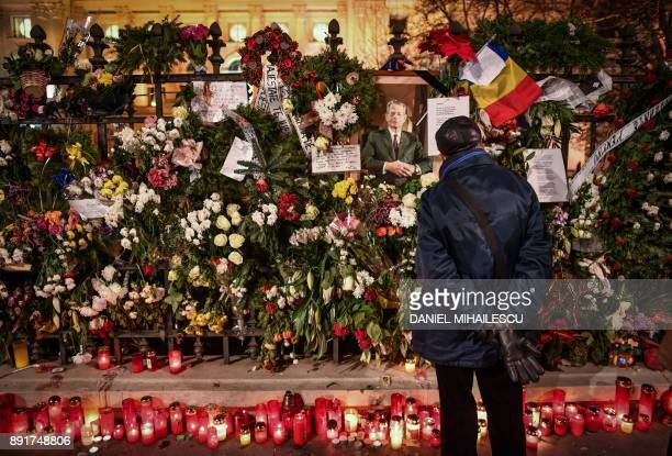A man stands in front of flowers displayed on December 13 2017 on the grills of the former Royal Palace that houses the National Arts Museum in...