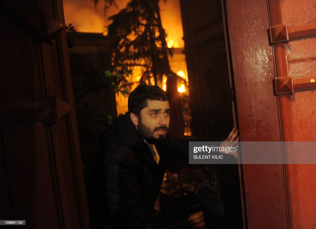 A man stands in front of Galatasaray University gate as Istanbul fireteams try to control flames during a fire at the University on January 22, 2013, in Istanbul.
