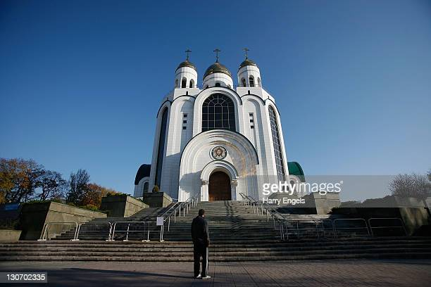 A man stands in front of he Russian Orthodox Cathedral of Christ the Saviour on October 28 2011 in Kaliningrad Russia Kaliningrad is one of thirteen...