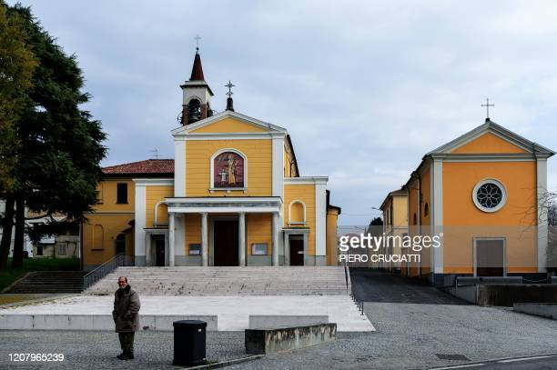 A man stands in front of the Giussano's Church of Robbiano where Don Giuseppe Corbari parson celebrated mass in a empty church pews adorned with...
