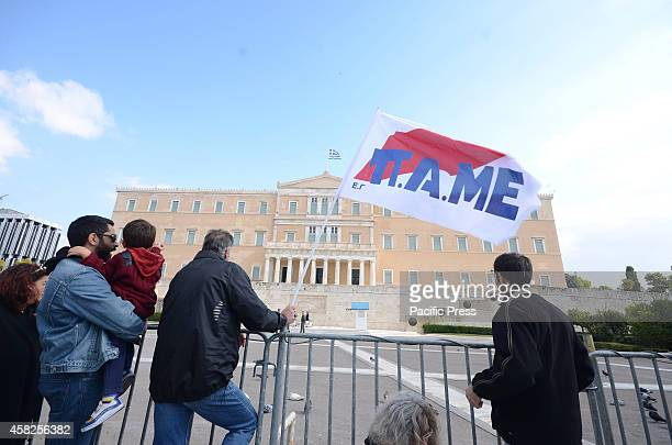 Man stands in front of the Greek Parliament holding a PAME union flag. Greek PAME union organised a demonstration in Syntagma square against the...