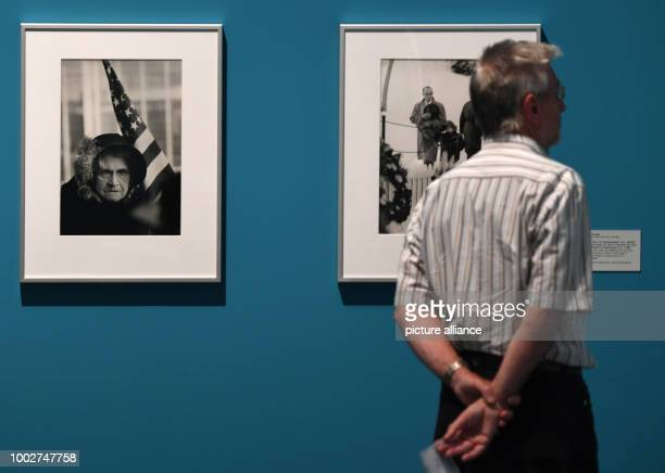 A man stands in front of the photo 'Alte Dame auf einem Festwagen bei der Parade zum 4 Juli in San Francisco' by Thomas Hoepker at the exhibition...