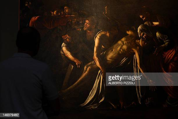 A man stands in front of the restored Caravaggio's painting 'Resurrection of Lazarus' at the Palazzo Braschi museum in Rome on June 15 2012 Painted...