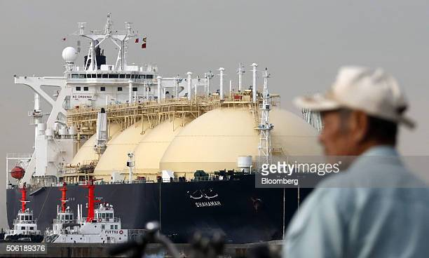 A man stands in front of the Shahamah liquefied natural gas tanker berthed at Tokyo Electric Power Co's Futtsu gasfired thermal power plant in Futtsu...
